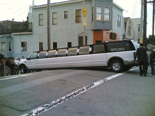 Stretch Limo SUV goes over a bump and gets stuck.  This photo is pretty funny, and I bet the wedding party was not planning on this!
